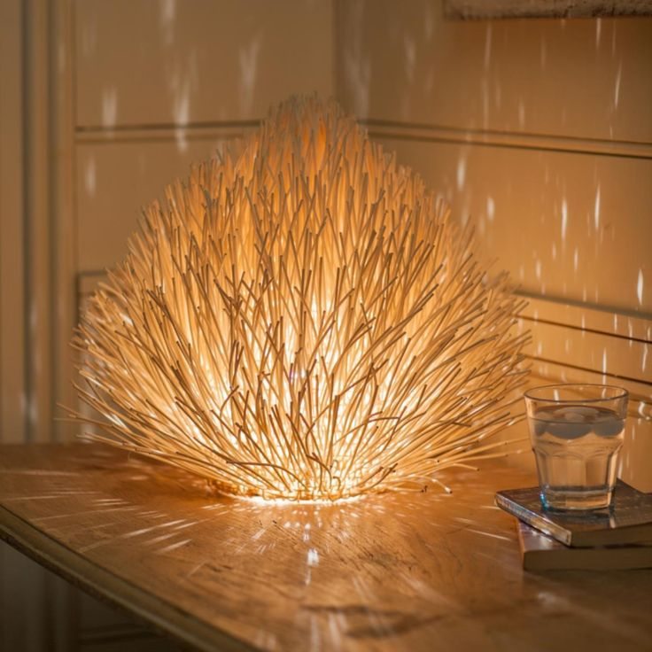 This lamp will add drama to your decor with its intriguing shape that radiates a sparkling effect when lit. Handwoven rattan. Fair trade.