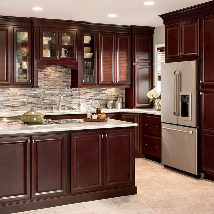 Cherry kitchen cabinets with oak floors and a mosaic backsplash create a  great traditional look.