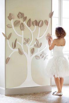Un arbre de vœux en papier  Grâce à quelques morceaux de papier, un bel arbre se dessine sur un mur et permet aux invités de laisser des messages aux mariés.