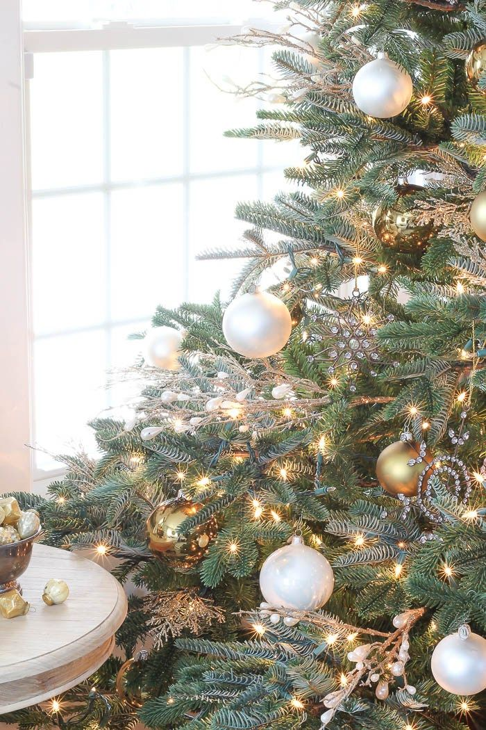 Christmas tree decorated with white and gold ornaments and glittered tree picks