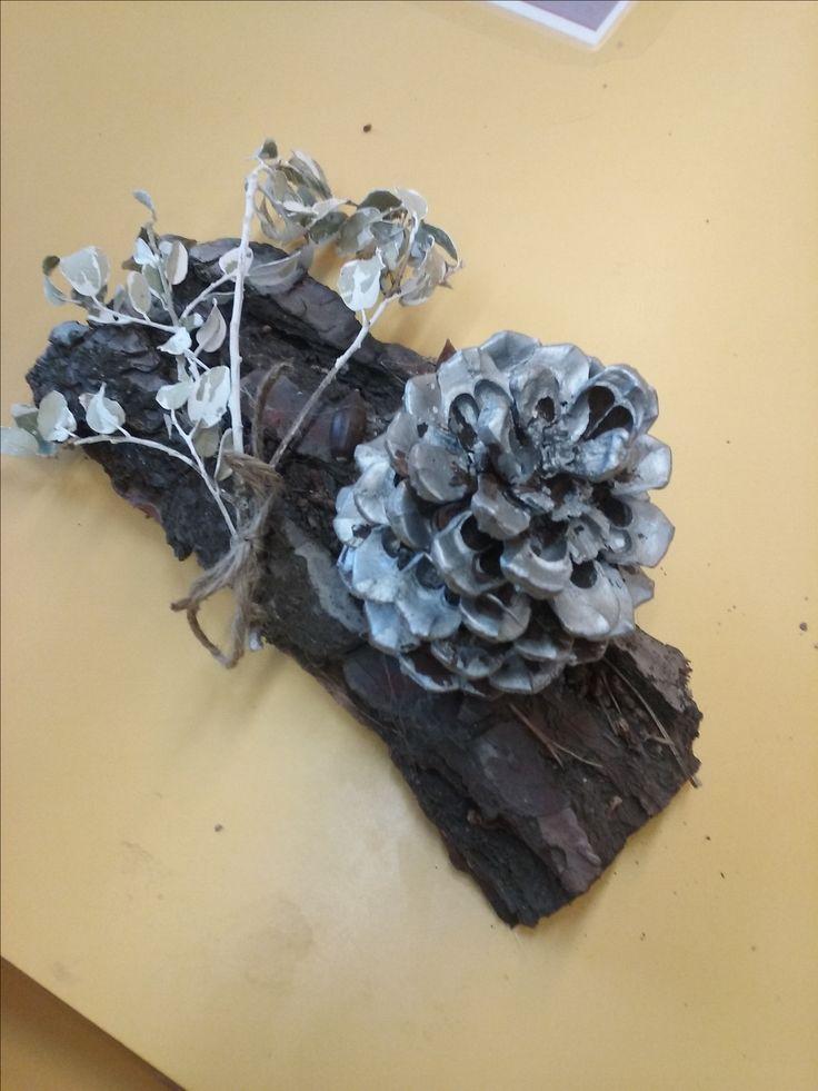 Centre de taula: Materials Naturals, escorça d'arbre, pinya i branca amb fulles pintada de blanc, també es pot col.locar una espelma