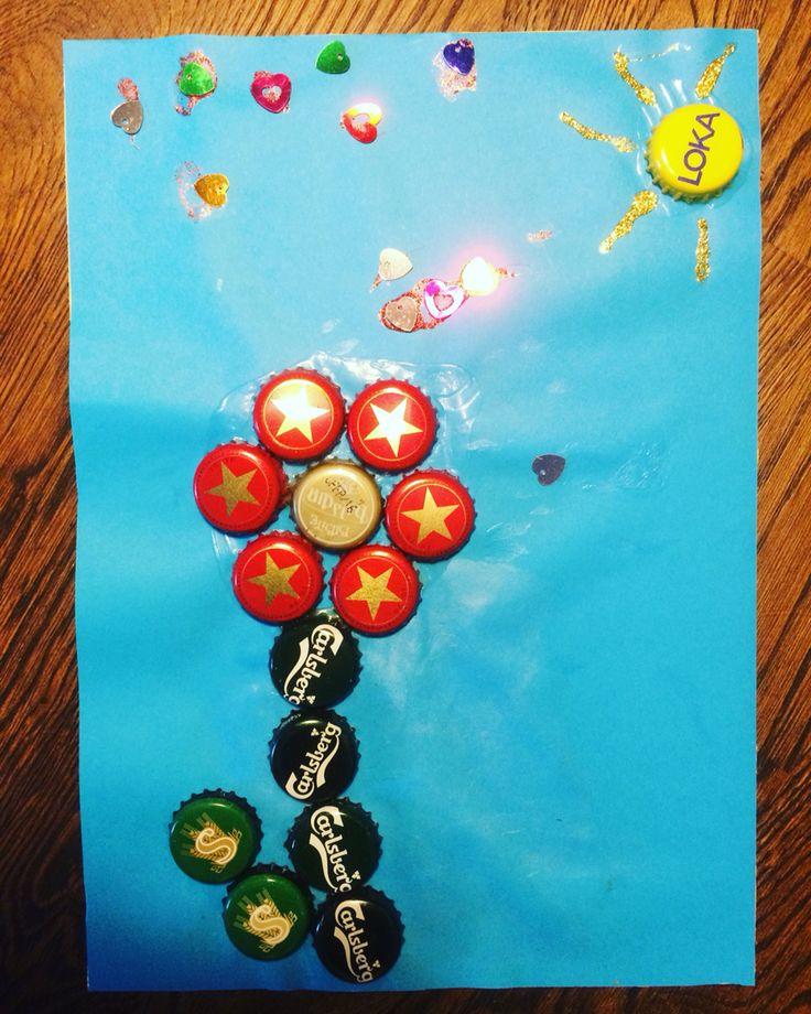 Pyssel med kapsyler, limmade på papper. Blomma och sol. Diy crafts caps