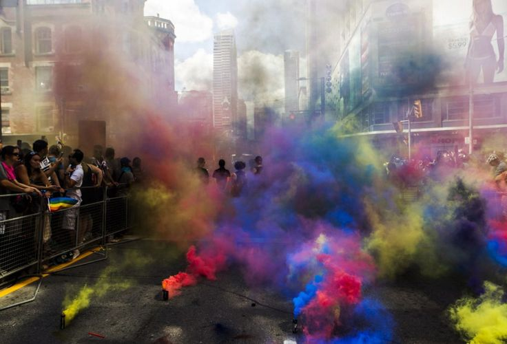 Members of the Black Lives Matter movement stand amidst coloured clouds from smoke grenades at the annual Pride Parade, in Toronto on Sunday, July 3, 2016. #Toronto
