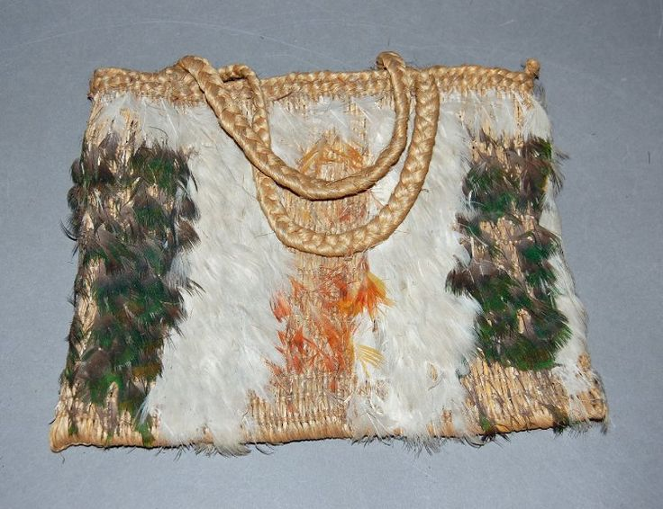 Bag made of woven flax, green, orange and white feathers (chicken and parrot?). Two plaited handles.