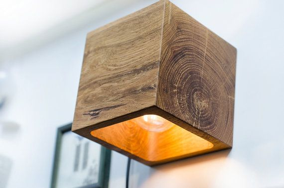 Wooden wall lamp with simple functional design. This cube has two options: switch is located aside, or with wire. We only use recycling wood, no trees were harmed during the making of this product :)  Solid block of OAK with accent on natural wood texture. Polished and smoothed by hands using durable safe materials for best resistance, and natural wax to make a perfect shiny surface. Beautiful design thing for fine style appreciators! Nothing more than just a simple form and emphasized…