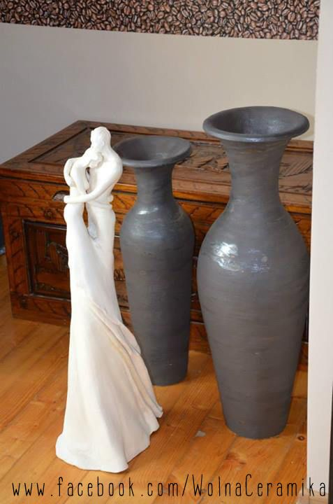 Sculpture of cuddled couple and vases.