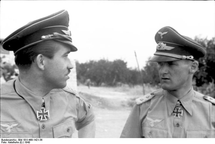 German Luftwaffe Major General, and ace fighter pilot, Adolf Galland (left) speaking to another officer while inspecting an airfield in southern Italy, 1943.