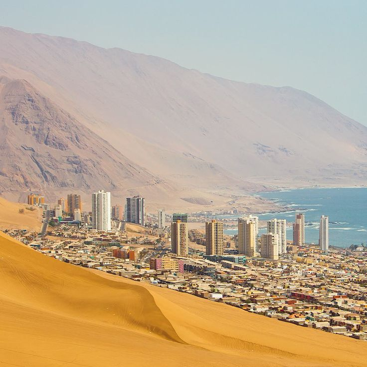 """National Geographic Travel on Instagram: """"The coastal city of #Iquique built on the desert sands of the Atacama Desert in #Chile. The long sand dune in the foreground is the tail of Cerro Dragón (Dragon Hill). According to the 2012 census, Iquique has a population of roughly 180,600 people. Photo by Mike Theiss @ExtremeNature"""""""