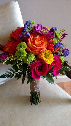 Bright and bold wedding bouquet with orange & hot pink roses, yellow and pink zinnias, craspedia, green button mums and purple statice wrapped in twine.