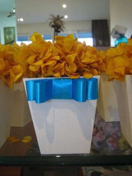 Lindo arranjo de Hortência Desidratada cor amarelo no cachepot em MDF branco, com laço de cetim chanel cor azul turquesa, cores vivas! Por si só já darão seus destaques em suas festas!  Hortências disponíves nas seguintes cores:  VERDE,LARANJA,AMARELO,MARFIM,VERMELHO,PINK,LARANJA,ROSA,AZUL,ROXO,LILÁS  Na hora do pedido favor informar: cor das flores+cor da fita  Arranjo ideal para várias situações como:decoração festa de casamento - lembrancinha ou de casamento ou festa infantil ou noivado…