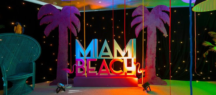 miami beach theme event with peacock chair, photo op giant letter sign, glitter palms and star cloth wall