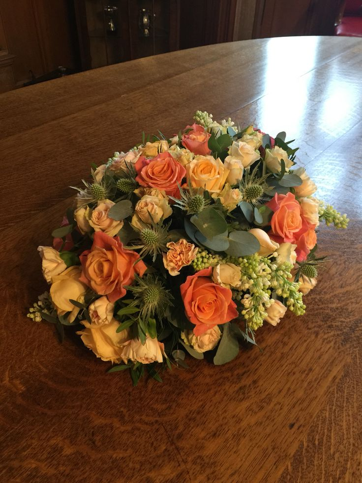 One of Suzanne's wedding table centrepieces with miss piggy roses, peach Avalanche roses, peach spray roses, Apple tea carnations, white astilbe, white lilacs, pistacia and Eryngium.