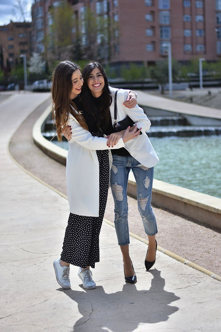 Lucía and Claudia Peris wearing white maxi coat, polka-dot wide leg trousers, white trainers, black crop top, ripped jeans, black pumps, high heels, white blazers, black bag (midilema.com)
