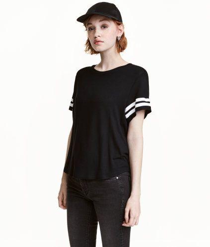 Svart. En t-shirt i mjuk viskostrikå med motiv.