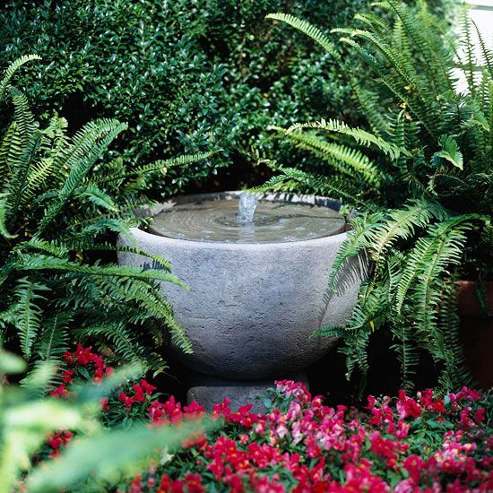 A simple fountain is often the perfect addition to an informal garden. Here, the fountain is made of cast stone and offers clean lines and a natural shape. Water flows from a disk on top into the basin below. The simple water feature creates an elegant setting, calmed by the soothing sound of running water. Lower the water level in the basin for a more pronounced sound, or raise it for a softer appeal.