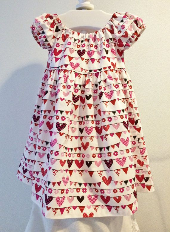 Red & pink hearts, flowers & bunting adorn this pretty little Valentine's Day peasant style toddler dress.  Empire length bodice with a full gathered skirt and puffy little sleeves will be perfect for an afternoon Valentines Day party at school, or for any other occasion!!  Toddler Size 3T - 4T $35.00  Baby Suzanna Johanna