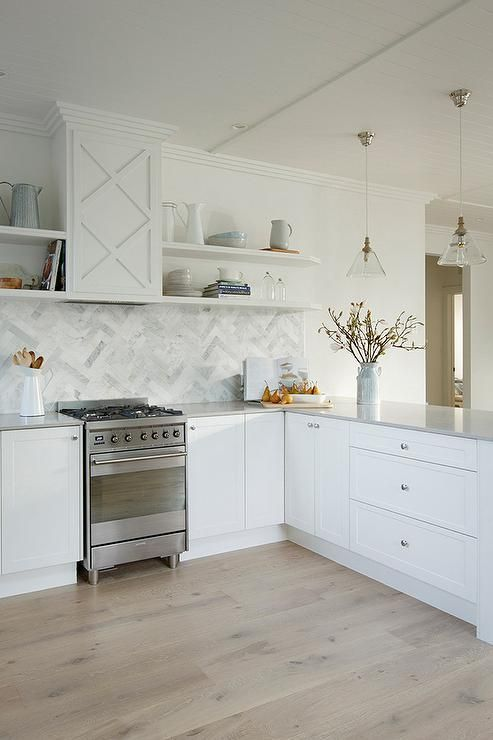 Beautiful kitchen features white shaker cabinets paired with light gray quartz countertops, Caesarstone Clamshell Quartz, and a marble herringbone backsplash.