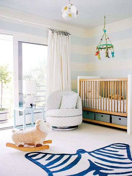 This South Carolina nursery is full of bold, contemporary design. Love the hand-painted sky blue stripes on the wall and the faux-zebra rug. Thick white curtain panels and an overstuffed swivel chair add  luxurious necessities.