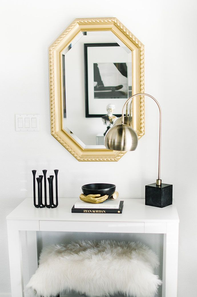 Entryway with a gold mirror, a lamb stool, and a gold arc lamp
