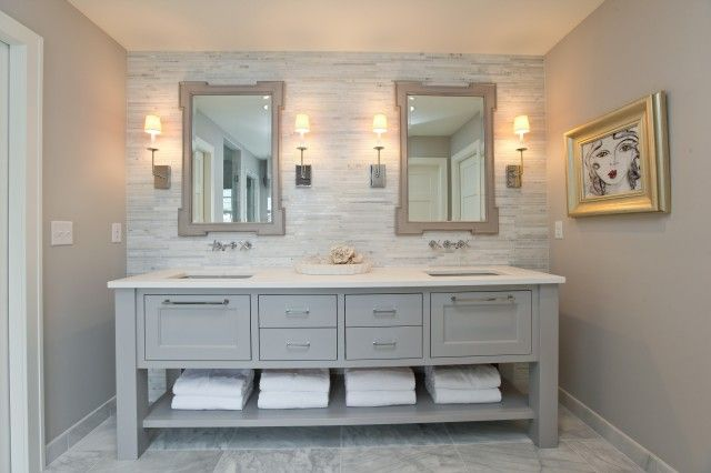 Beautiful monochromatic bathroom for two with gray walls paint color, gray-ish blue double bathroom vanity with white quartz countertop, mosaic marble linear stagger tiles backsplash, wall-mount faucets, marble tiles floor and gray mirrors.