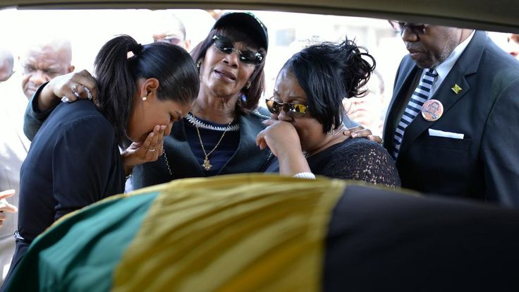 Ministers Lisa Hanna, Prime Minister Portia Simpson Miller and Neita Headley cry when former Minister Roger Clarke's body arrives at Norman Manley International Airport.