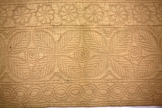 Maker:Welsh Rural Industries Date:1930 - 1939  Peach cotton poplin wholecloth quilt with hand quilted leaves, flowers and cable motifs...