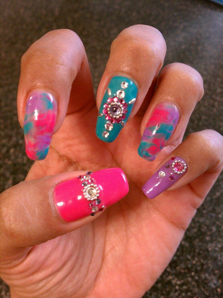 Pink, purple, and teal marbling with rhinestones calgel manicure design.