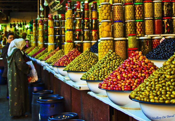 Postcard from the souks    A series of my favourite images would be incomplete without this one, definitely one of my best from last year.    The colours are great, love the depth of field but the most amazing of all is …… how do they do that? Piling up those olives must be a herculean task of dexterity and concentration, but even more confusing is how do they close up without losing them all over the floor?