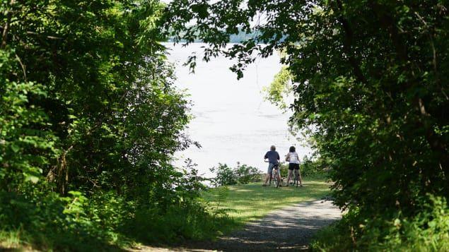 Des cyclistes admirent la vue de Laval à partir de l'île Perry.