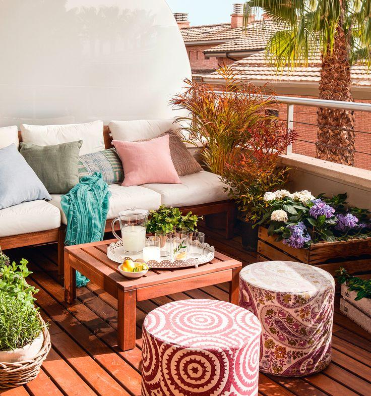 Terraza pequeña con suelo entarimado, sofá de madera y cojines blancos, mesa de centro y pufs redondos boho