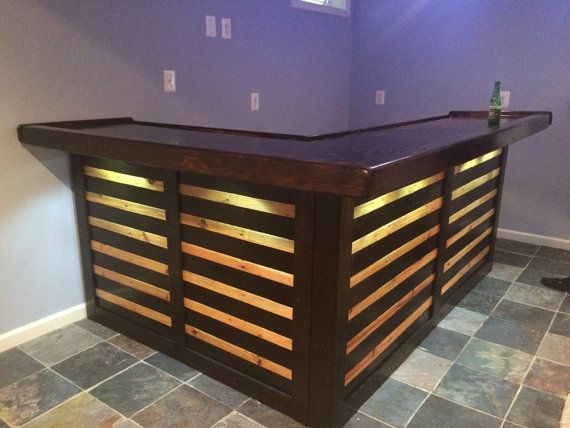 Custom made Pallet Bar from reclaimed pallets wood. L Shaped bar I can do in a variety of sizes - 6 feet by 4 feet, 8 feet by 4.5 feet, 9 feet by 5.5 feet, or custom size. The bar top comes in your choice of plywood (Pine, Sande, Birch, Oak, Maple, Walnut, etc.) The height of the bar is 42 inches. You have your choice of stain color and polyurethane. The bar top is 3/4 inch by 20 inches wide. Under that is another 3/4 inch by 24 inches wide sheet that makes up the bottom of the bar ...