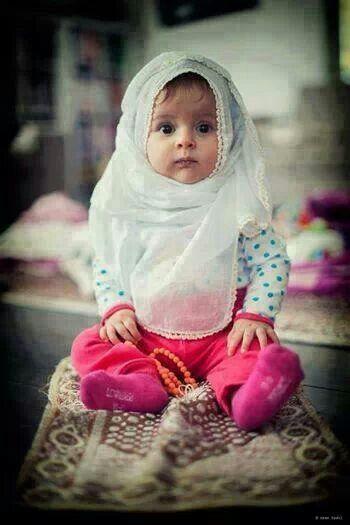 Cute Muslim baby girl praying.