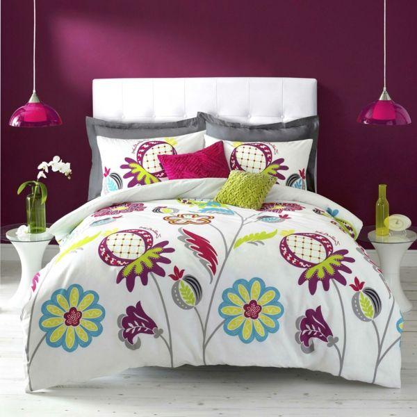 un mur pourpre et deux lampes suspendues, deux petites tables rondes et un lit de couette blanche à fleurs multicolores