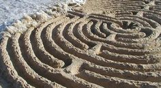 Sand labyrinth being washed away