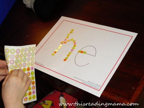 placing stickers on letters to form a word and work on fine motor- part of a FREE Reading curriculum for advanced preschoolers | This Reading Mama