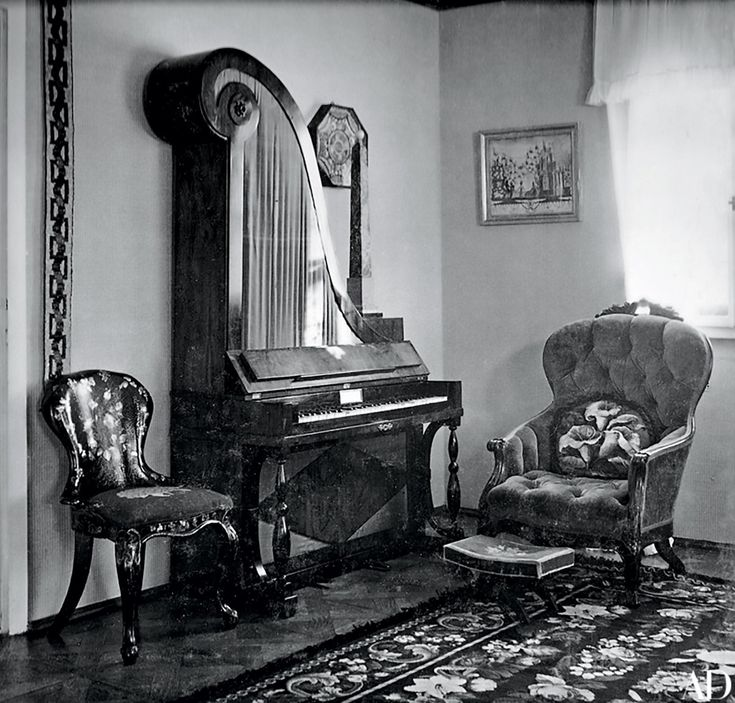 The interiors of the chalet were decorated with 19th-century furnishings that moved from house to apartment over the years. Shown in the late 1930s, the living room contained an antique Biedermeier vertical piano flanked by a Victorian papier-mâché side chair; a flowered needlework carpet covers the floor.