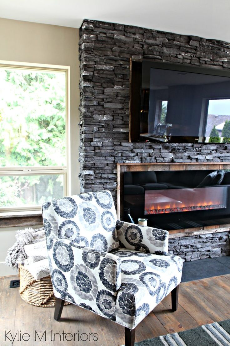 Charcoal ledgestone fireplace update with reclaimed rustic wood surround and window ledge, rustic wood flooring and Urban Barn accent chair
