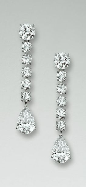 """PAIR OF DIAMOND PENDENT EARRINGS, """"NIAGARA"""", CARTIER Each brilliant-cut diamond weighing 1.63 carats respectively suspending a line of five brilliant-cut diamonds terminating in a pear-shaped stone weighing 3.43 and 3.60 carats respectively, signed Cartier and numbered, French assay and maker's marks."""