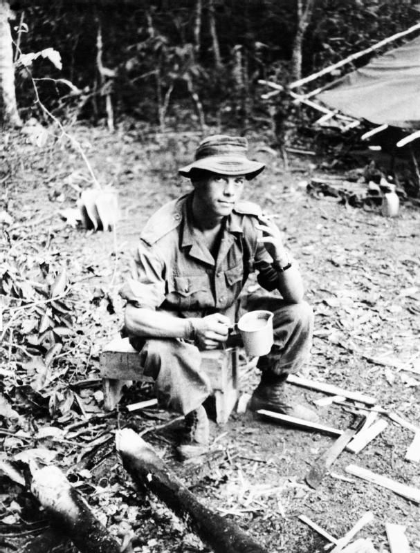 Lance Corproral Andrew Robb, on a jungle patrol,probably of the 1st Battalion, The Cameronians (Scottish Rifles), rests with a cup of tea & a cigarette - Malaysia - 1948-50