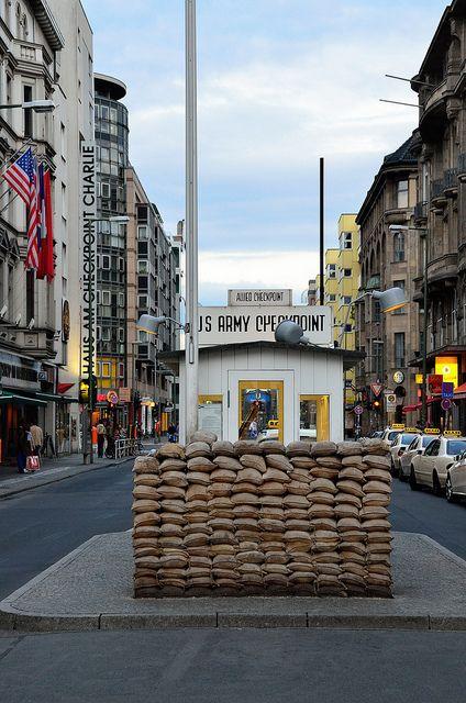 Jour 2. Checkpoint Charlie (& Museum on the left) Berlin, Germany. C'est l'un des postes frontières berlinois qui, lors de la Guerre froide, permettait de franchir le mur qui divisait la capitale allemande entre le secteur Ouest et le secteur Est. Curiosité, en 2010, un établissement McDonald's a pris la place du « Snackpoint Charlie » qui regroupait des vendeurs de kebab, de sushis et de pizzas.