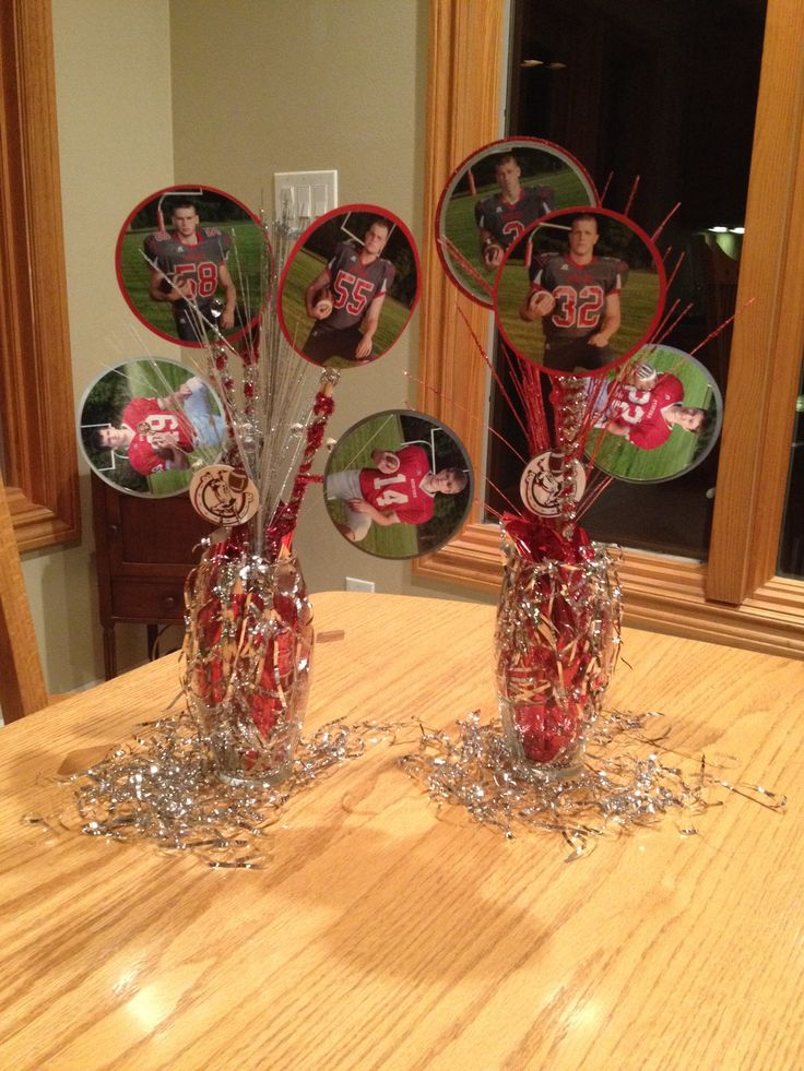 """Football banquet centerpiece  Used football vase, with foam inside and metallic wrapping paper to hide it. I used kabob sticks (cheap enough and a bag has about 50)  I found mini """"Popsicle sticks"""" and hot glued each stick together. Each picture was cut and glued to a piece of card stock, the popsicle stick then was glued in between each card stock piece.  I made these around Christmas time, I was able to find alot of silver and red supplies to add some pizzazz:)"""
