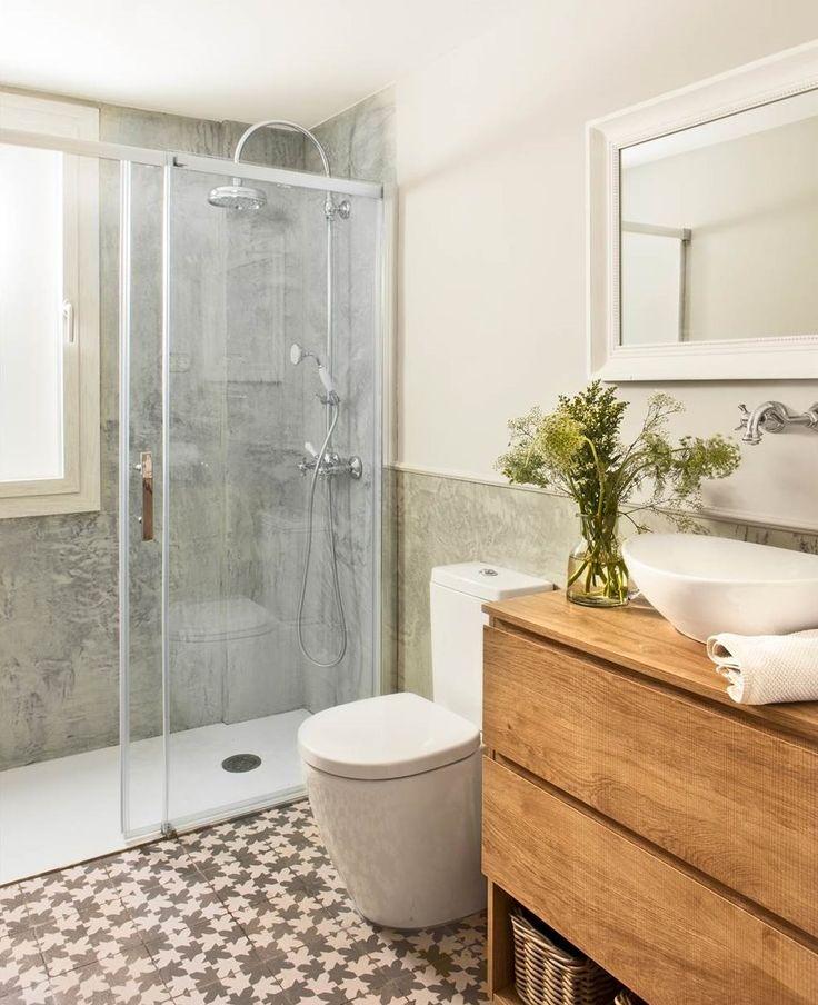 Baño con suelo de baldosas hidráulicas, mueble de lavabo de madera, ducha de microcemento con mampara y espejo con marco blanco