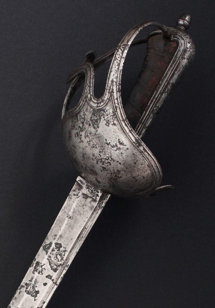 """J33BZ.- Espada de oficial para Caballería de Línea, modelo de 1803. España, 1802-1808. Guarnición de hierro: cazoleta de hierro con doble guardamano, gavilán intermedio en """"S"""" y anillo para el pulgar, monterilla larga y perilla. Hoja recta, filo al exterior, lomo cuadrado con canal contiguo en sus 3/4, resto a tres mesas. Inscrita en el lomo """"RL. FAB …"""".Long. total 101 cm; hoja 85,5 cm; anchura base hoja 31 mm."""