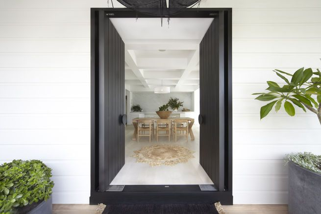 Sydney house by Burley Katon Halliday - the house retains its original white weatherboard cladding. New double doors, painted black to contrast the house's neutral palette, open directly to a kitchen and dining space.   Image by Sharrin Rees.