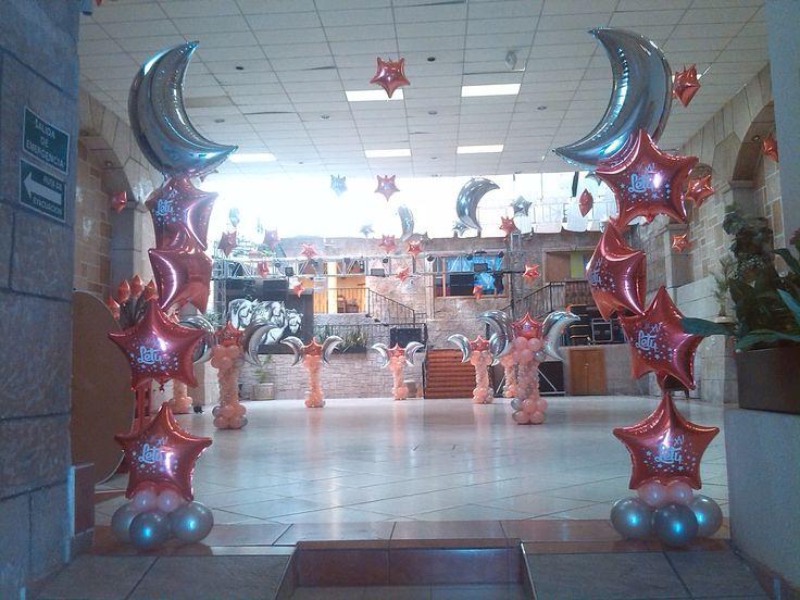 Decoración con impresión personalizada en los globos de estrellas y lunas con gas helio en la entrada del salón y colgando al techo de la pista en colores plata y coral para armonizar