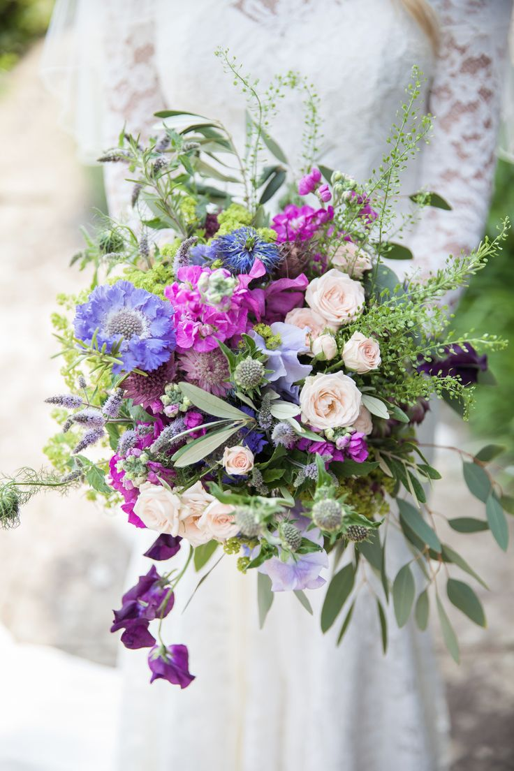 Rustic summer bridal bouquet for festival insired wedding at Northbrook Park. Flowers created by Eden Blooms Florist from Lilac Scabious,Flowering Mint, Nigella Pods, Deep Pink Astrantia, Raspberry Stock, Lilac Sweetpea, Bombastic Spray Rose, Olive, Nigella, Green Bell, Alchimilla Mollis & Eucalyptus. Image by www.kerryannduffy.com