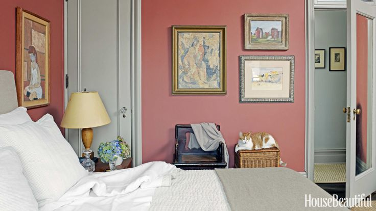 This Manhattan apartment's master bedroom is painted Farrow & Ball Picture Gallery Red and Charleston Gray. Designer Alexander Doherty was inspired by the palette of the galleries' walls at the Metropolitan Museum of Art. Laptop the cat poses beneath a Thomas McKnight streetscape and an anonymous beach scene. Priscilla Alexander painted the abstract portrait over the Chinese chair, as well as the portrait next to the bed.