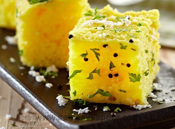How to make Khaman Dhokla-Fermented gram flour and yogurt batter steamed, cut into cakes and tempered with mustard seeds and topped with fresh coriander and grated coconut.