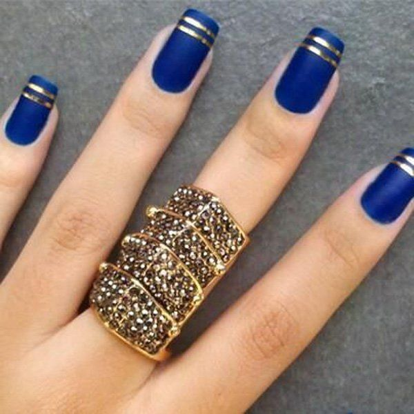 The thin gold stripes look simply amazing against the royal blue matte colored nails.