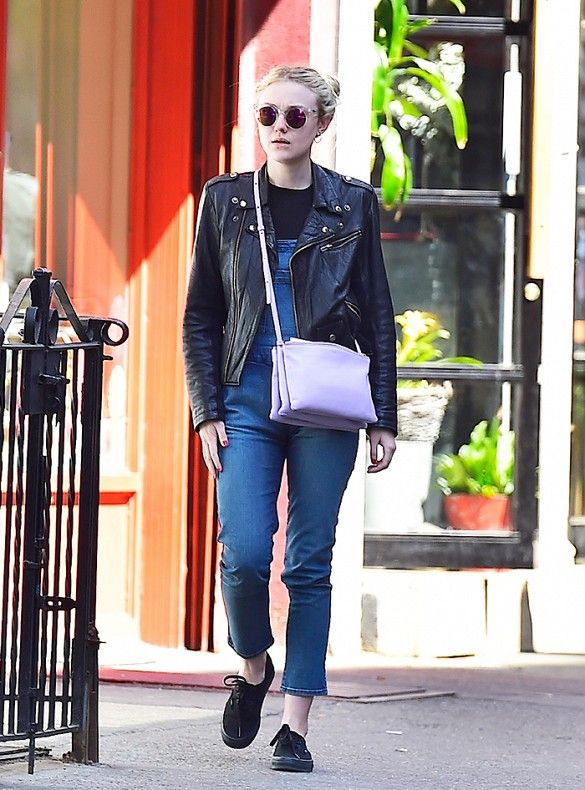Dakota Fanning wore denim overalls with a moto jacket, a purple crossbody bag, black sneakers from Vans and circle sunglasses.